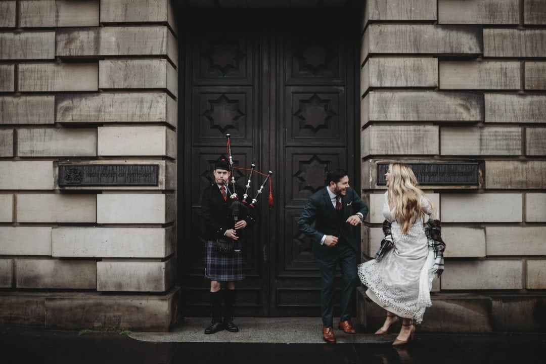 Happy elopement couple dancing in the rain with bagpiper in Edinburgh City Centre, Royal Mile