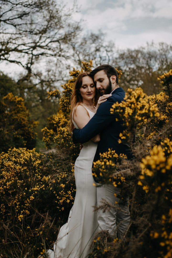 Couples shoot in nature Scotland by yellow gorse bush. Lena Sabala and Patrick Zaarour on Mark Pacura workshop.