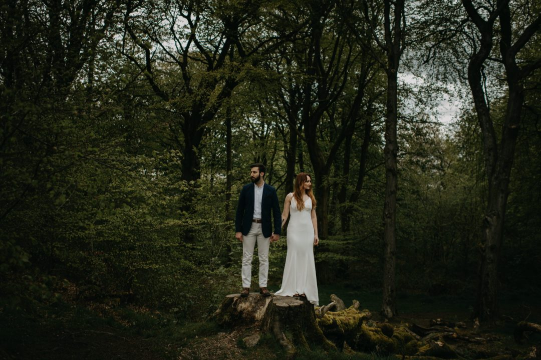 Couple standing on log in Scottish forest whilst eloping in Scottish Highlands