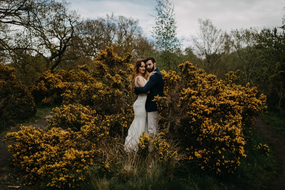 Couples shoot in nature Scotland by trees and gorse bushes. Lena Sabala and Patrick Zaarour on Mark Pacura workshop.