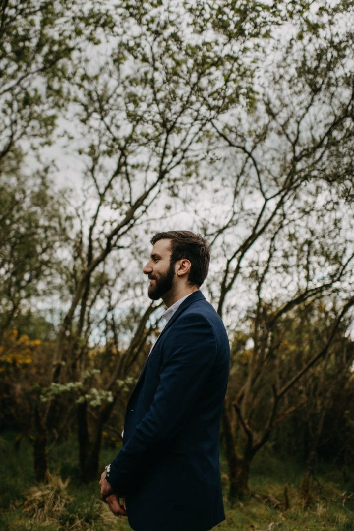 Groom in nature Scotland by trees. Lena Sabala and Patrick Zaarour on Mark Pacura workshop.