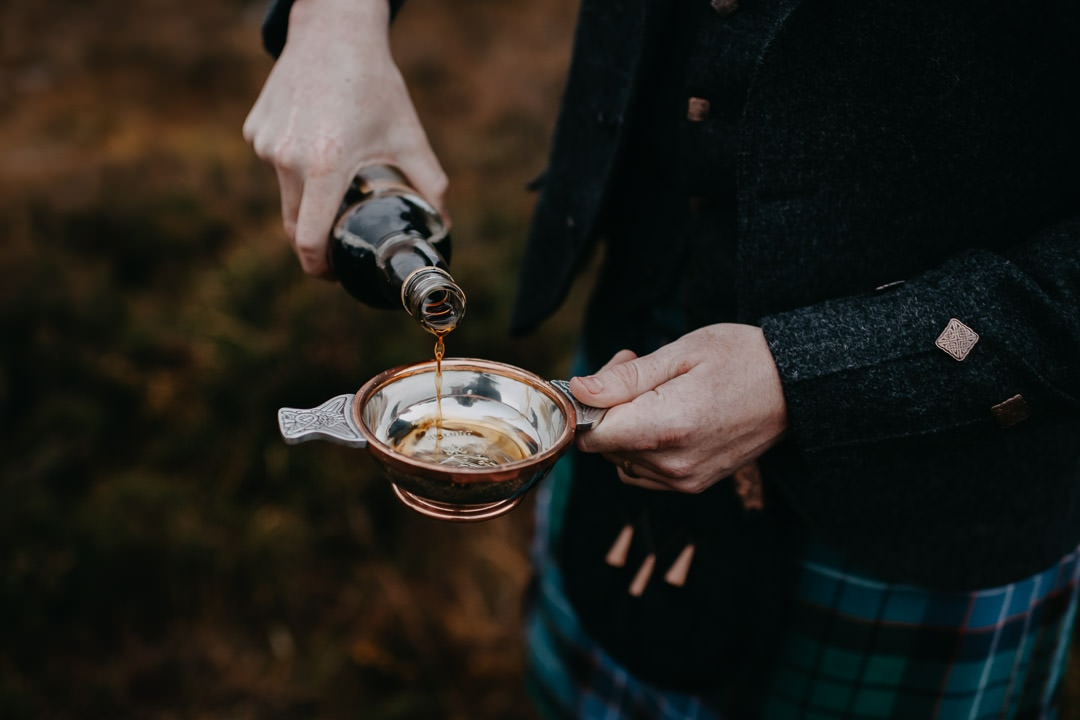 Pouring quaich with lindisfarne mead in Glencoe - Scottish tradition