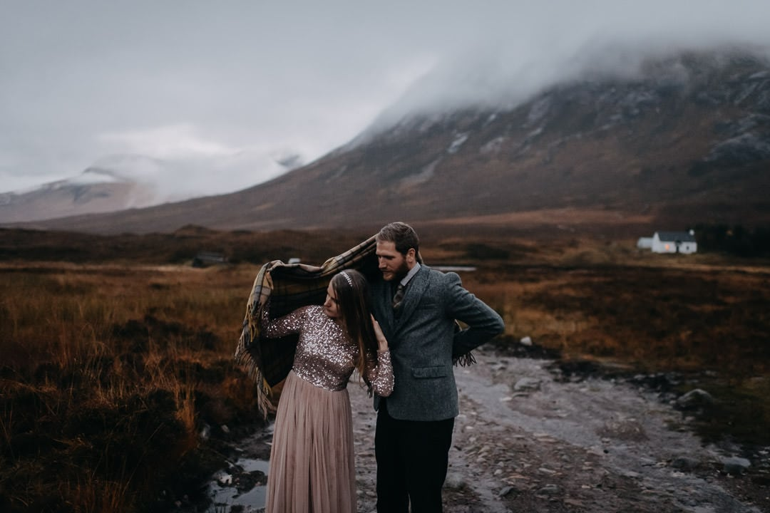 Elopement couple adventure session with tartan blanket at foggy Glencoe
