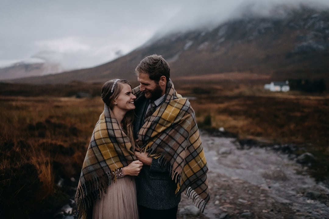 Happy elopement couple in Glencoe - tartan blanket in the rain