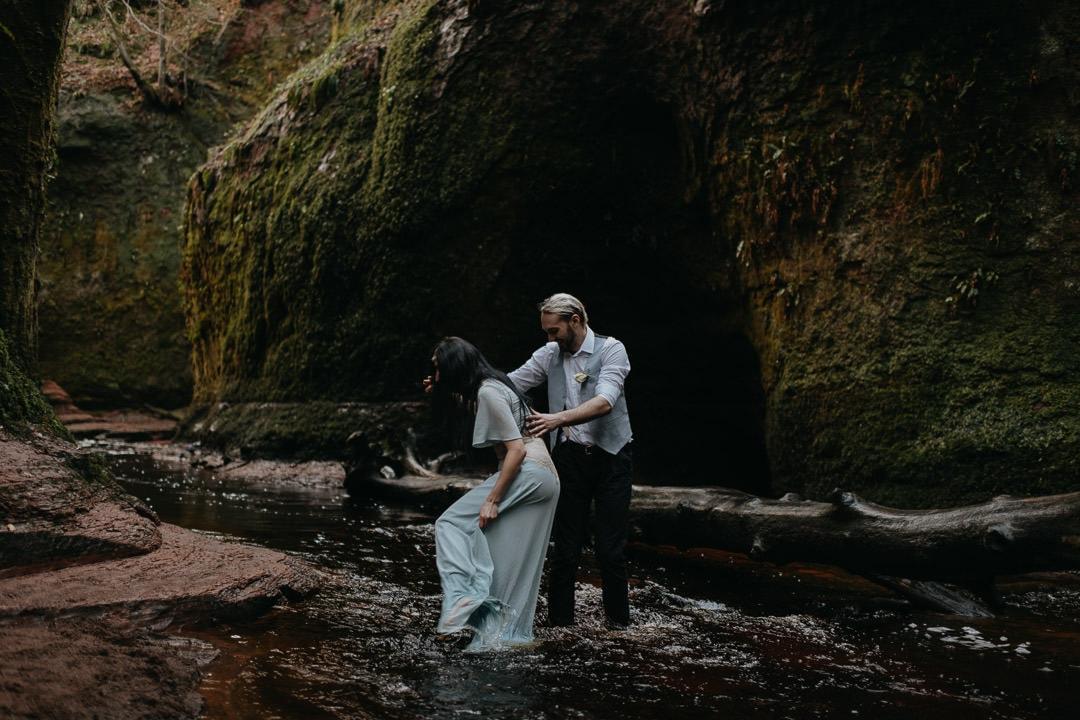 Adventurous elopement couple walking in The Devil's Pulpit, Glen Finnick