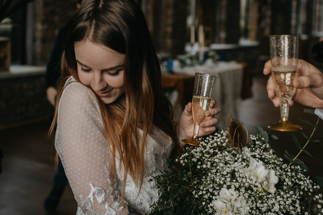 Happy bride at the national mining museum, popping champagne - scottish elopement