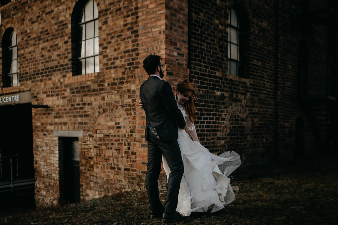 Couple with windy hair and dress outside the Newbattle Mining Museum - Scotland elopement photographer