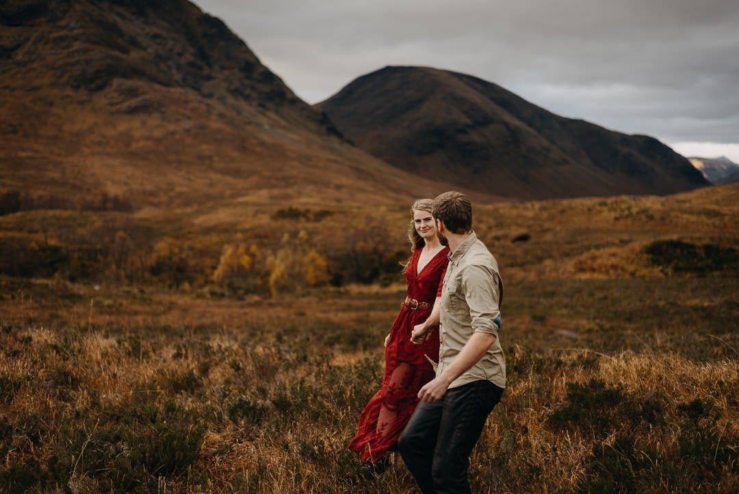 Couple snuggled together next to Buachaille Etive Mòr in Scottish Highlands mountain scenery during photo adventure session