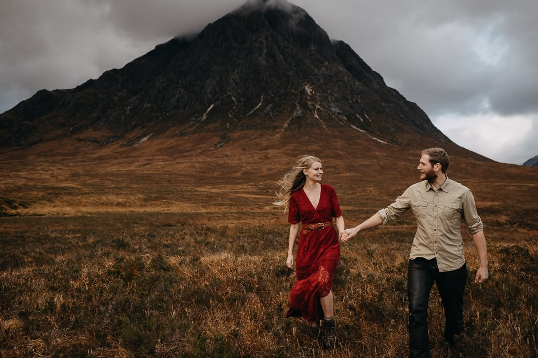 Couple walking through the grass in front of Buachaille Etive Mòr near Glencoe - wearing a boho red dress