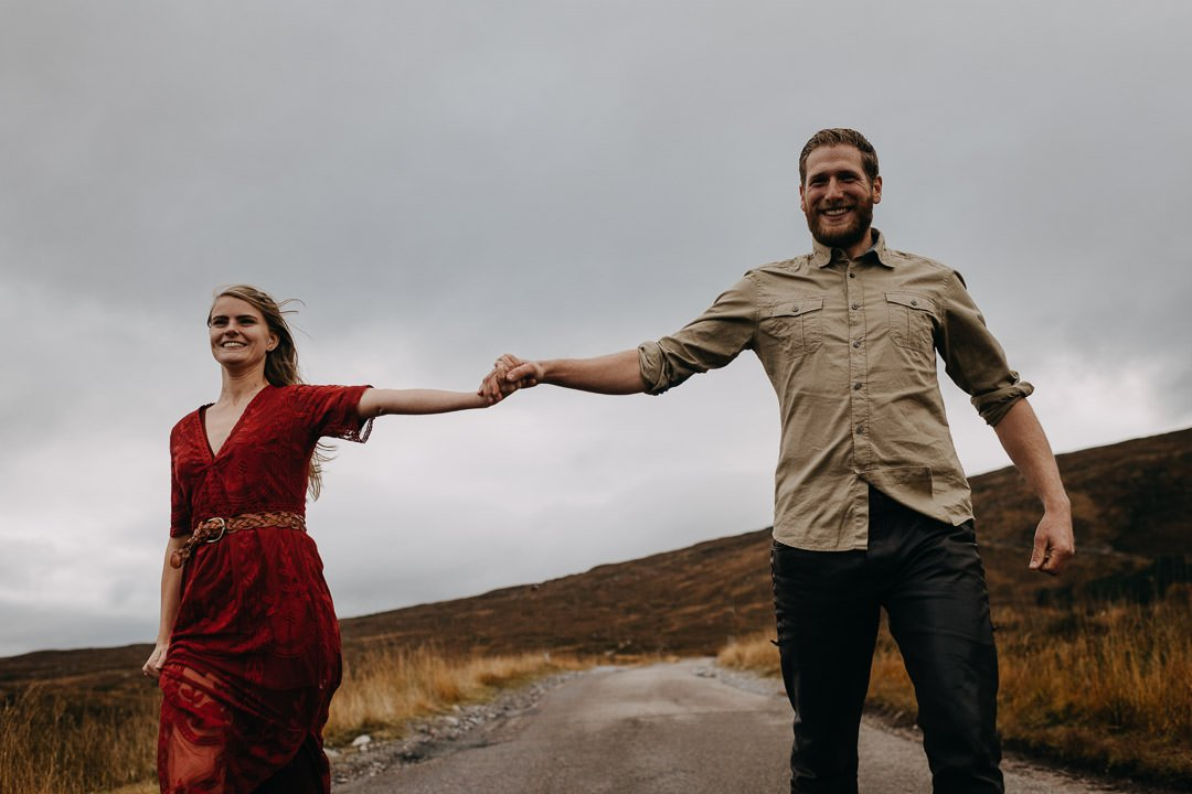 Gleeful couple running through the Scottish Highlands on an adventure photoshoot