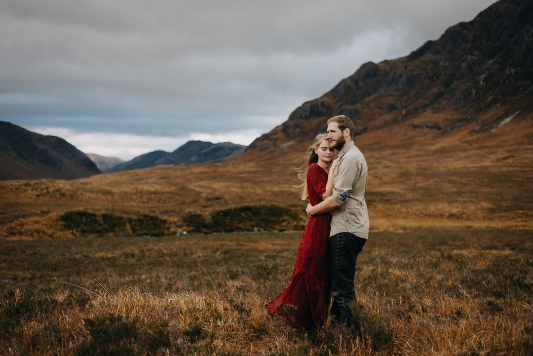 Cuddling couple in Buachaille Etive Mòr in Glen Etive in the Scottish Highlands who are on an adventure session
