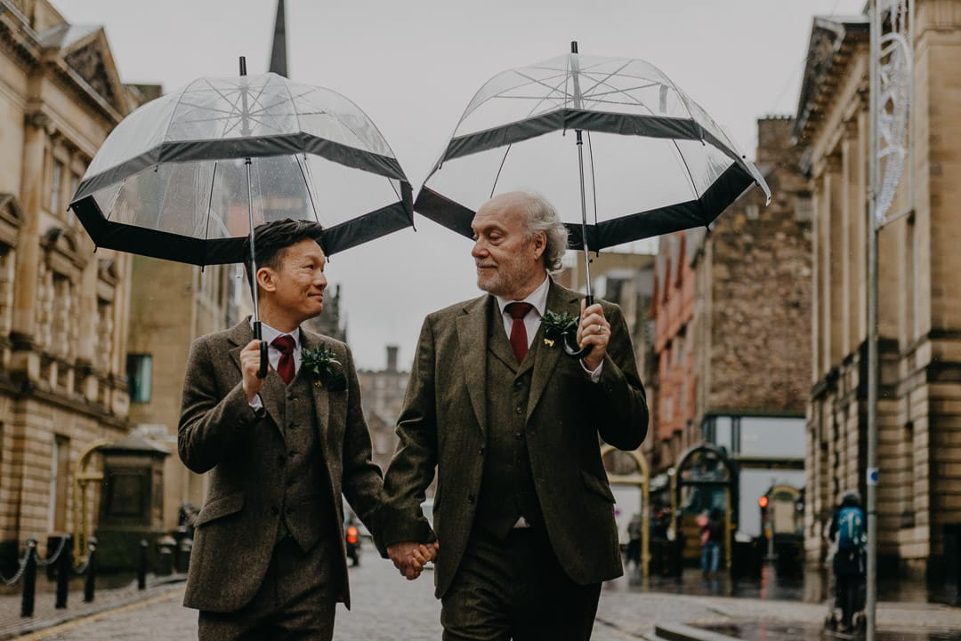 Edinburgh city centre elopement in the rain with umbrellas - gay couple