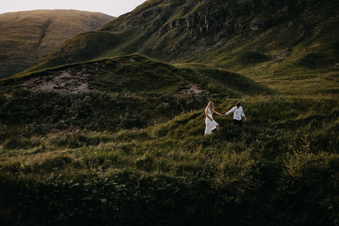 Eloping couple roaming the glen in the Scottish highlands