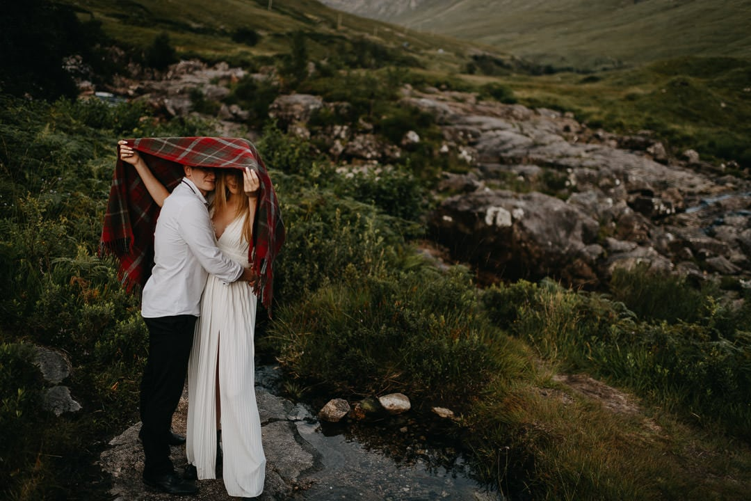 Elopement couple hiding under Tartan Blanket Co blanket from midges during Glen Etive elopement