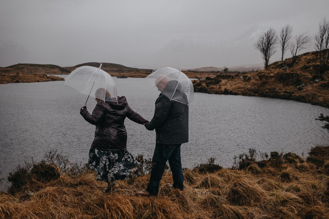 Walking through the moors on a winter rainy couples session in Glencoe