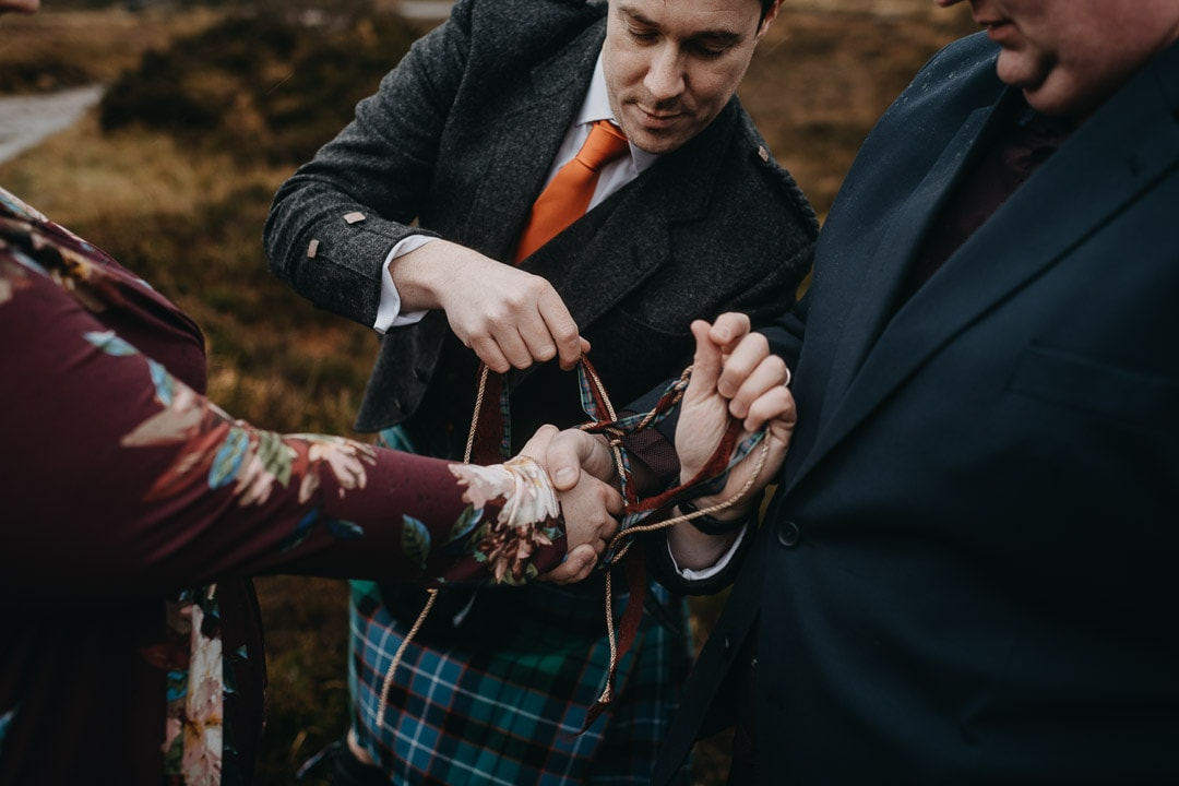 Romantic handfasting cord tying the knot in Glencoe during wedding anniversary photoshoot in Scottish Highlands
