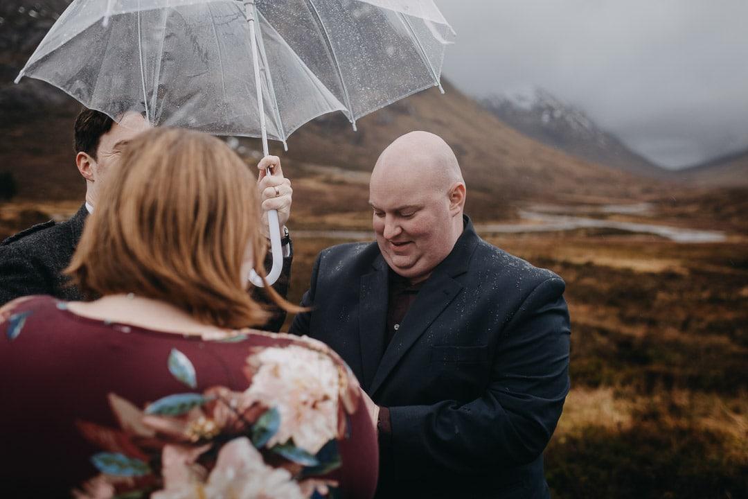 Romantic handfasting in Glencoe during wet wedding anniversary photoshoot in Scottish Highlands