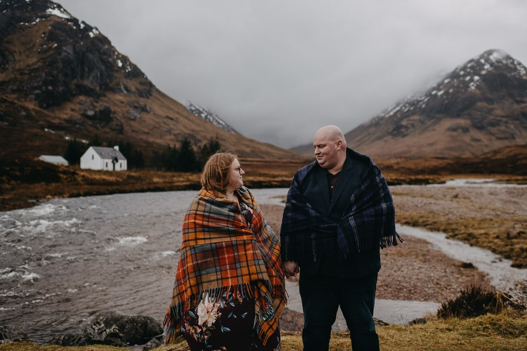 Buachaille Etive Mhor in Glencoe on romantic couples adventure session wearing a tartan blanket