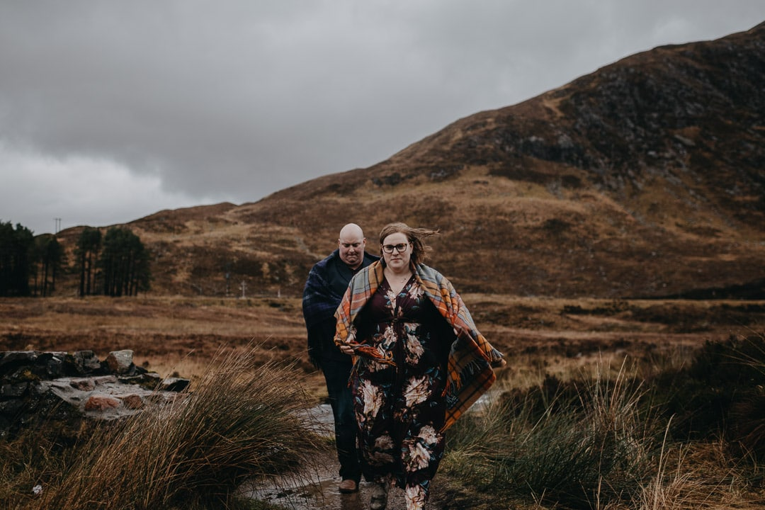 Exploring Buachaille Etive Mhor in Glencoe on couples adventure session wearing a Tartan blanket