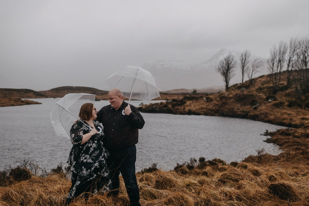 Holding umbrellas on a winter rainy couples session in Glencoe, Scotland
