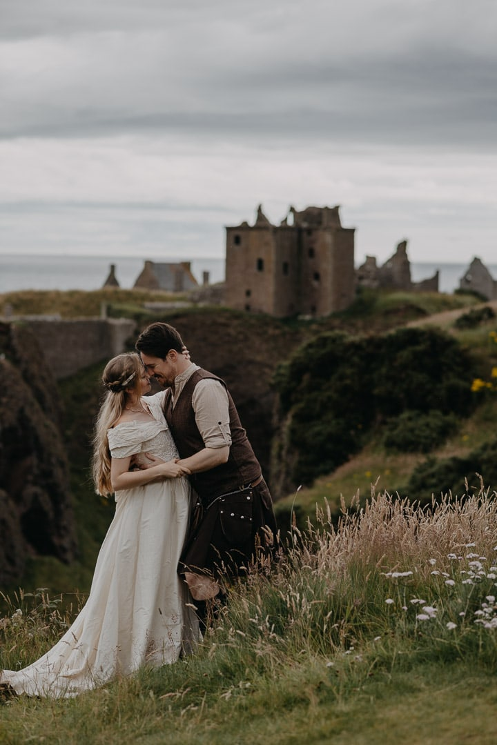 Dunnottar Castle elopement and proposal location in Scotland - couple hugging in front of Castle