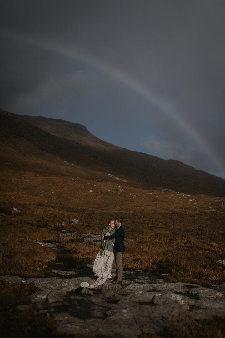 eloping couple under rainbow in glencoe